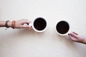 Två koppar kaffe som möts över ett bord. Varsin person håller i sin kopp, endast hand och handleder syns av vardera person.