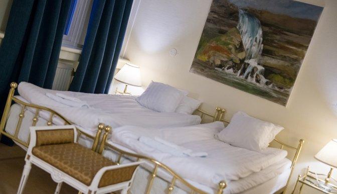Ett hotellrum med två enkelsängar bredvid varann. På väggen vid huvudänden hänger ett konstverk, en tavla. Rummet har mörkblåa gardiner.