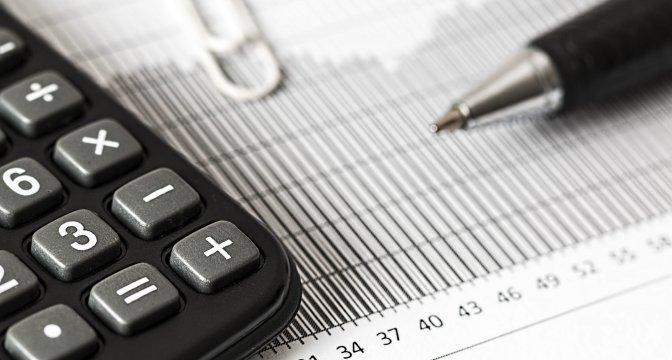 Närbild på ett papper med siffror och streck, kan tolkas som statistik. Ovanpå pappret ligger en miniräknare, en penna och ett gem.