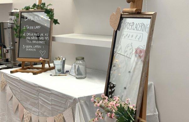 Bild från ett bröllop. Två olika stafflier med speglar där brudparet har skrivit instruktioner till gästerna på spegelglaset.