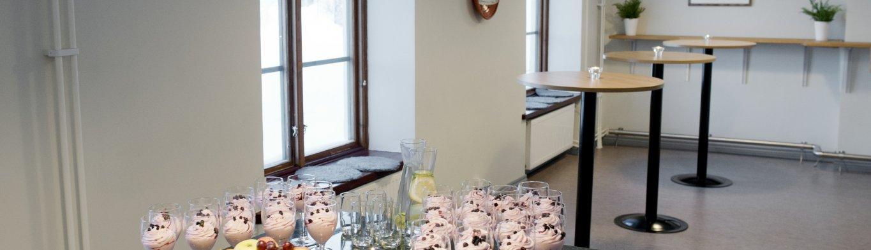 Ett bord fyllt med olika slags efterrätter, snacks och dryck. Konferensfika dukat i ett rum där konferensgäster kan ta en paus.