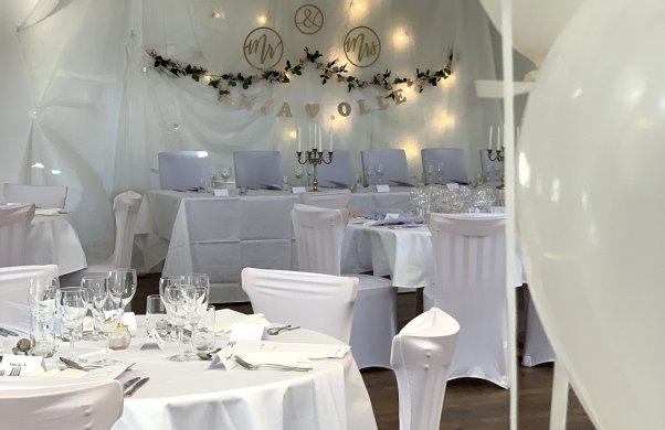 Bröllopsdukning med vita dukar och stolar. I bakgrunden syns brudparets plats med dekorationer på väggen. I förgrunden syns vita ballonger.