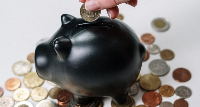 Svart spargris på vitt underlag. Runt om grisen ligger mynt i olika valörer. En hand håller i ett mynt och är på väg att lägga ett mynt i spargrisen.