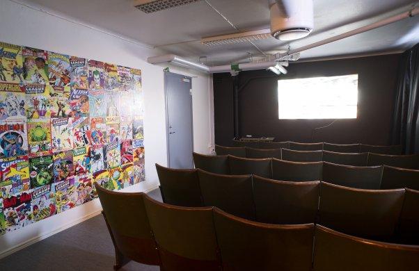 Biorummet. Här syns biostolar i rött på rad, en vit bioduk längst fram och på vänster sida syns gamla serietidningar uppsatta på väggen.