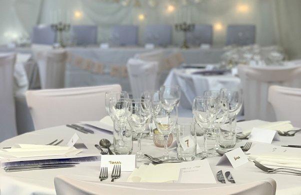 Bröllopsdukning med vita dukar och stolar. I bakgrunden syns brudparets plats med dekorationer på väggen.