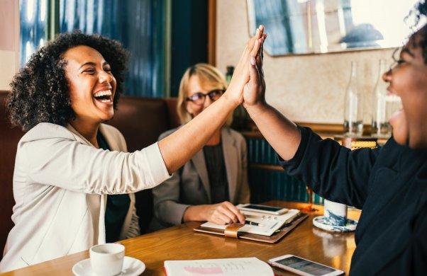 Tre personer sitter vid ett bord och skrattar. Två av dem gör en high five.