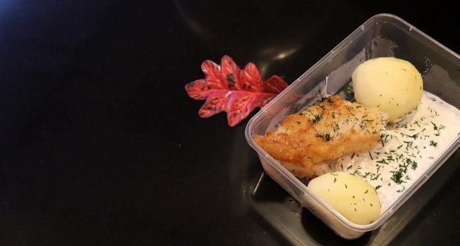 Matlåda med fisk, potatis och sås. Matlådan står på svart underlag och intill lådan syns ett rött höstlöv.