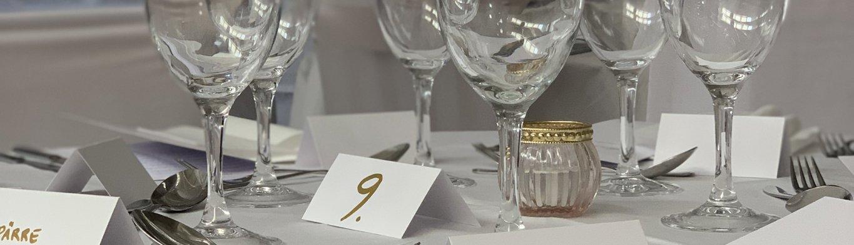 Bröllopsdukning helt i vitt. Närbild på vinglas, lappar med namn, servetter och bestick.